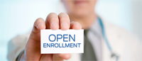 Photo of man holding open enrollment card